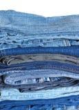Pile sur beaucoup de jeans d'isolement sur le plan rapproché blanc Photographie stock