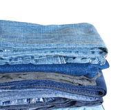 Pile sur beaucoup de jeans d'isolement sur le plan rapproché blanc Photographie stock libre de droits