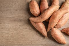 Pile of sweet potatoes and space for text on wooden background. Top view royalty free stock images