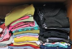 Pile of T-shirt clothes in closet. Stack of many color folded woman shirts overlay stock images