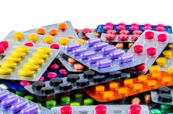 Pile of tablet pills on white background. Yellow, purple, black, orange, pink , green tablet pills in blister pack. Painkiller medicine. Drug for migraine stock photo