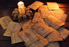 Pile of the tarot cards with candle. Pile of the tarot cards in candle light. Halloween and magic still life, fortune telling seance or black magic ritual with stock images