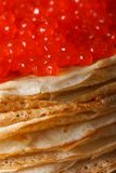 A pile of thin crepes with red caviar macro. vertical Stock Images