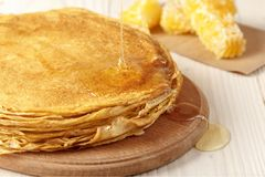 A pile of thin pancakes on the table. A pile of thin hot pancakes on a light wooden surface and pouring honey on them royalty free stock photography