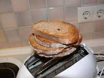 Pile of toast on toaster. Overhead view of pile of toast on electric toaster in kitchen Stock Photography