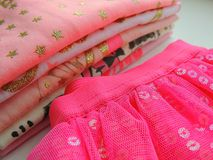 Pile of toddler cotton pink white clothes. Glittered tops and skirt. Royalty Free Stock Images