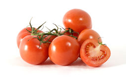 A pile of tomatoes. Shot on a clean white background with one tomato cut in half Royalty Free Stock Photo