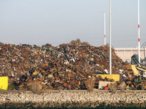 Pile of trash at Recycling processing facility along shore Royalty Free Stock Images