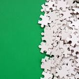 A pile of uncombed elements of a white jigsaw puzzle lies on the background of a green surface. Texture photo with copy space for. Text Stock Image