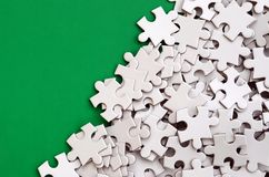 A pile of uncombed elements of a white jigsaw puzzle lies on the background of a green surface. Texture photo with copy space for. Text Stock Photography