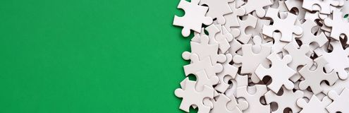 A pile of uncombed elements of a white jigsaw puzzle lies on the background of a green surface. Texture photo with copy space for. Text Royalty Free Stock Photo