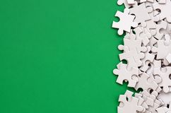A pile of uncombed elements of a white jigsaw puzzle lies on the background of a green surface. Texture photo with copy space for. Text Royalty Free Stock Images