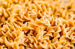 Pile of uncooked curly pasta noodles Stock Photo