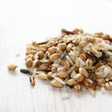 Pile of uncooked multigrain rice on white wooden background Royalty Free Stock Image
