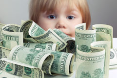 Pile of United States dollars and baby on a background. Pile of United States dollar hundred USD banknotes on white table and blurred baby looking on it on a Royalty Free Stock Photo