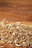 Pile of unpeeled oat grains on wooden background, top view, close-up, macro, selective focus. Some copy space. Dietary food. Vegan background. Healthy eating Stock Photo