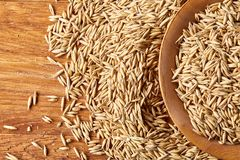 Pile of unpeeled oat grains on wooden background, top view, close-up, macro, shallow depth of field. Pile of unpeeled oat grains on wooden background, top view Royalty Free Stock Photo