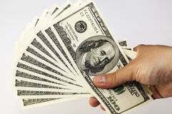 Pile of US Dollars. Close-up of man hand holding  a pile of 100 dollars isolated on white background Stock Photos