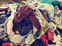Pile of used clothes on sale in a flea market, filtered royalty free stock image