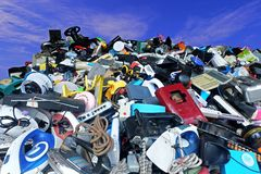 Pile of used Electronic and Housewares Waste Division broken or damage with blue sky and clouds background. For Reuse and Recycle concept Stock Image