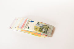 Pile of used Euro notes of assorted denominations. Stacked on top of one another on a white background with copyspace in a conceptual financial image Royalty Free Stock Image