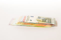 Pile of used Euro notes of assorted denominations. Stacked on top of one another on a white background with copyspace in a conceptual financial image Stock Images