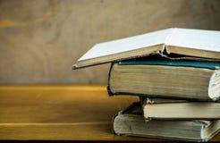 Pile of used old opened books, shabby corners, aged wood desk, university education, reading concept. Close up stock images