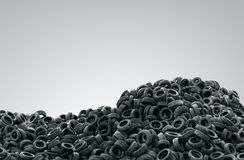 Pile of used rubber tyres on gray background