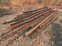 Pile of used rusty rails. Stock of steel rails at old closed railway station.  Metal material Royalty Free Stock Photo