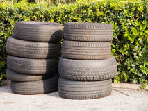 Pile of used worn out tyres green bushes in background Royalty Free Stock Photography