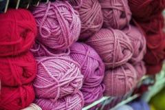 Pile variée de fil à tricoter pour tricoter aux nuances de pourpre, rose, violet Stock de marchandises pour la créativité et Photos libres de droits