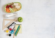 A pile of various stationery on table, notepad, colored pencils, ruler, marker, planer, space for text. Delicious school lunch box. Sandwich and fruit. The Royalty Free Stock Photography