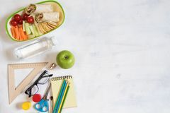 A pile of various stationery on table, notepad, colored pencils, ruler, marker, planer, space for text. Delicious school lunch box. Sandwich and fruit. The Royalty Free Stock Photo