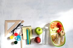 A pile of various stationery on table, notepad, colored pencils, ruler, marker, planer, space for text. Delicious school lunch box. Sandwich and fruit. The Stock Photo