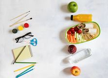 A pile of various stationery on table, notepad, colored pencils, ruler, marker, planer, space for text. Delicious school lunch box. Sandwich and fruit. The Stock Image