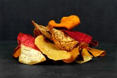 Pile of vegetable chips on a black background Stock Photo