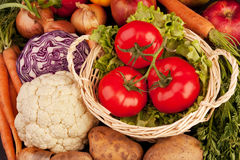 Pile of vegetables. Three tomatoes in basket, lettuce, onions, carrots, half of cabbage, cauliflower and potatoes Stock Photos
