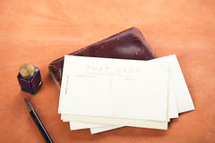 Pile of vintage post cards with  ink pen, inkpot on leather tabl Stock Photo