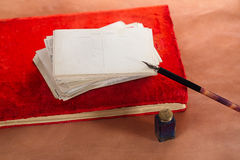 Pile of vintage post cards on red album with  ink pen, inkpot on Royalty Free Stock Photography