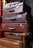 Pile of suitcases. Pile of vintage suitcases on armchair Royalty Free Stock Image