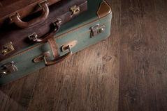 Pile of vintage suitcases. Vintage luggage close-up on dark hardwood floor, travelling concept Royalty Free Stock Image