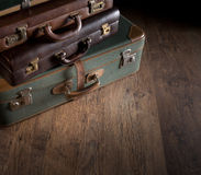 Pile of vintage suitcases. Vintage luggage close-up on dark hardwood floor, travelling concept Stock Image
