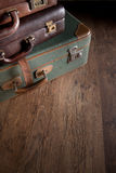 Pile of vintage suitcases. Vintage luggage close-up on dark hardwood floor, travelling concept Royalty Free Stock Images