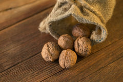 Pile of walnuts in shellin a bag on a wooden background . Linen Stock Photo