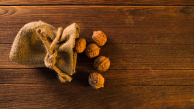 Pile of walnuts in shellin a bag on a wooden background . Linen Stock Photos