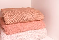 Pile of warm autumn and winter knitted sweaters on a home wardrobe shelf. Modern fashion clothes in shades of living coral. Pile of warm autumn and winter stock photos