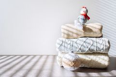 Pile of warm knitted sweaters with Christmas ornament and toy snowman on wooden table on light background. Winter cozy clothes background, mock up with copy stock images