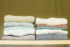 Pile of warm sweaters on a shelf. Two piles of warm sweaters for fall or winter on a shelf in a closet. Soft draped background Stock Images