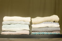 Pile of warm sweaters on a shelf Stock Photo