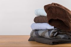 A pile of warm sweaters on a wooden table on a light background. winter clothes royalty free stock photo